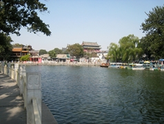 Boats, buildings, trees, and a walkway along the edge of Shicha Hai, an artificial lake in Beijing, China