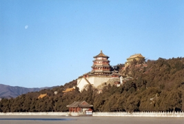 Under the moon in a blue sky, the main building of the Summer Palace rises above Kunming Lake near Beijing, China