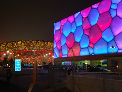 The multicolored exterior of the Water Cube, or National Aquatic Center, in Beijing, China, with the Bird's Nest in the background