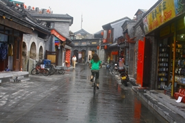 A woman riding a bike down a narrow street in a hutong area in Beijing, China