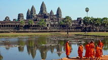 A group of orange-clad monks stands before the towers of Angkor Wat, Cambodia