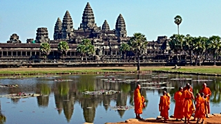 A group of monks in orange robes stands together in front of the towers of Angkor Wat, Cambodia