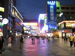 Crowds of people walk along a brightly lit pedestrian street in downtown Chengdu (成都), China
