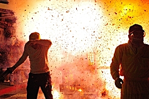 Spectators turn their backs and shield their faces during a massive Chinese New Year fireworks explosion