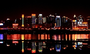 The brightly lit, modern buildings of the Chongqing waterfront reflected on the surface of the Yangtze River