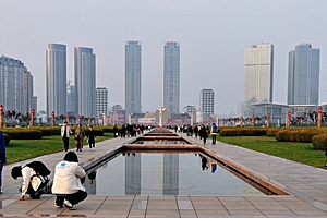 Skyscrapers reflect off the surface of a reflecting pool in Xinghai Square, Dalian (大连), China