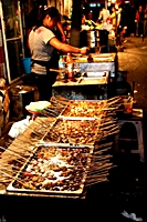 A street vendor sells food on skewers in Dalian (大连), China