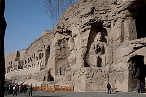 Grotto openings and Buddhist carvings on a rock face at the Yungang Grottoes near Datong (大同), China