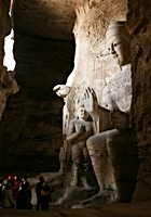 Tourists stand at the feet of a giant Buddha statue at the Yungang Grottoes near Datong (大同), China