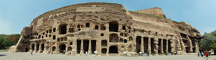 A panoramic view of grotto openings in the rock face at the Yungang Grottoes near Datong (大同), China