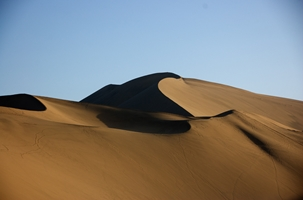 Smoothly contoured sand dunes under a blue sky near Dunhuang (敦煌), China