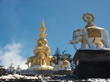 The giant Puxian Bodhisattva statue and a gilt temple building on Mount Emei's Golden Summit