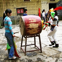 A colorfully dressed traditional drummer from China's Miao ethnic minority beats a large drum in Fenghuang (凤凰), Hunan Province, China