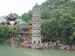 Crowds pack the shore of the Tuo River around Wanming Pagoda during a festival in Fenghuang (凤凰), Hunan Province, China