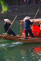 Boatmen push covered gondolas through the Tuo River in Fenghuang (凤凰), Hunan Province, China
