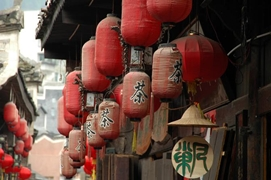 Traditional red paper lanterns hang along the front of a teahouse in Fenghuang (凤凰), Hunan Province, China