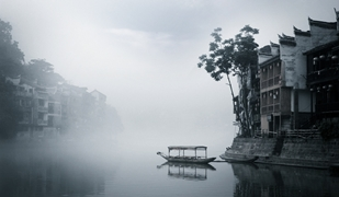 A covered gondola floats next to waterfront buildings on the misty Tuo River in Fenghuang (凤凰), Hunan Province, China