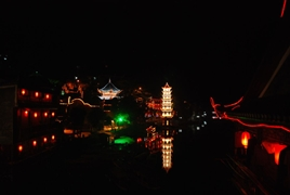 Wanming Pagoda and other waterfront buildings and lanterns glow on the Tuo River in Fenghuang (凤凰), Hunan Province, China