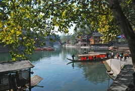 A view from under a green-leafed tree of tourists riding in covered gondolas on the Tuo River in Fenghuang (凤凰), Hunan Province, China