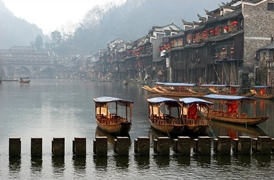 Covered gondolas float on the misty Tuo River in Fenghuang (凤凰), Hunan Province, China
