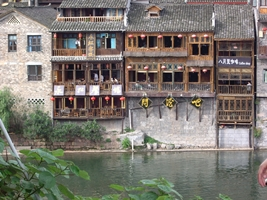 Traditional waterfront buildings converted into hostels, bars, and cafes line the Tuo River in Fenghuang (凤凰), Hunan Province, China