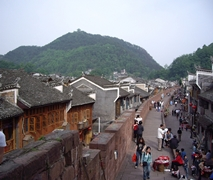 Crowds stroll along a long, curving street and wall in Fenghuang (凤凰), Hunan Province, China