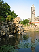 A tower stands next to a pond with a waterfall in Lingnan Impression Park in the Panyu District of Guangzhou, China