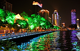 Brightly lit skyscrapers and trees on the bank of the Pearl River in Guangzhou, China