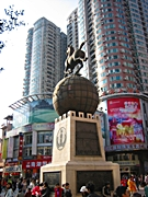 A statue of a horse atop a globe in a city square in downtown Guangzhou, China