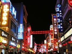 Nightlife, stores, and neon signs on a busy pedestrian street in Guangzhou (广州), China