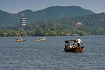 Sampans float on the surface of West Lake in front of Leifeng Pagoda and Jingci Temple in Hangzhou, China