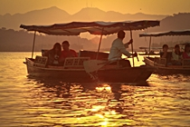 Tourists relax in covered rowboats on Hangzhou's West Lake at sunset