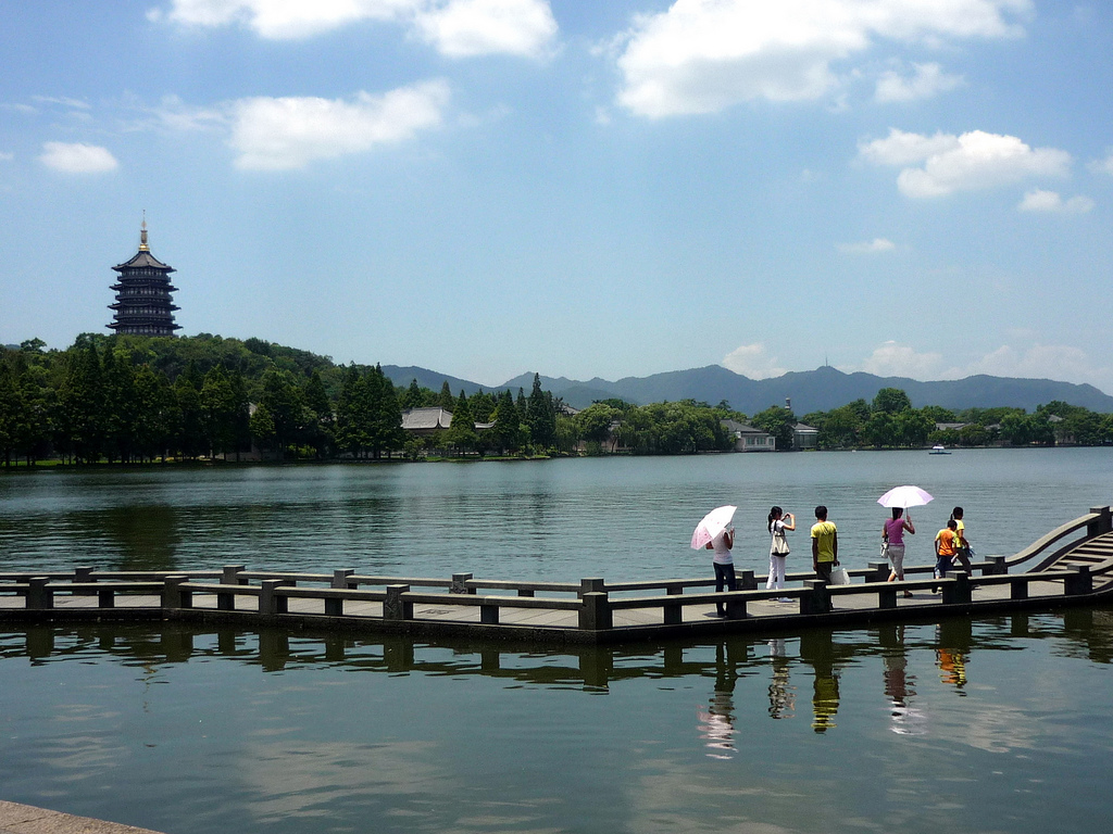 Tourists walk along a walkway on the water of West Lake with a pagoda on a hill in the background in Hangzhou (杭州), China