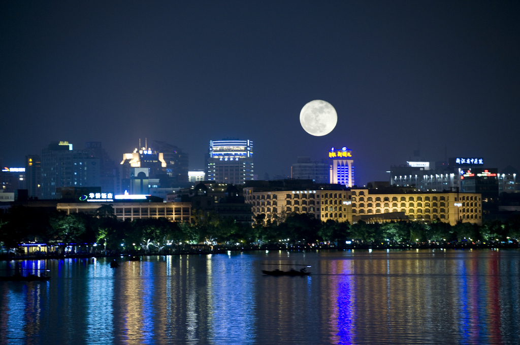 A full moon suspended over downtown buildings, as seen from West Lake, in Hangzhou (杭州), China