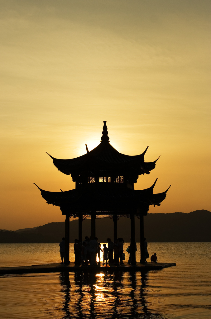 A small pavilion on the water of West Lake silhouetted by the setting sun in Hangzhou (杭州), China