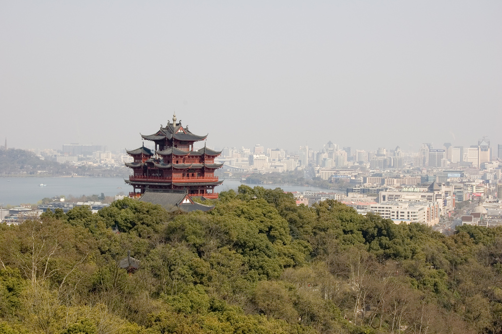 A large hilltop pagoda-like building overlooks West Lake and the downtown area in Hangzhou (杭州), China