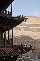 A mountain vista backdrop to a closeup view of the eaves of a building at the Hanging Temple, Hanging Monastery, or Xuankong Temple at Mount Heng (恒山), China