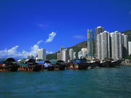 A row of fishing boats in Hong Kong's Aberdeen Harbour with high-rise apartments in the background
