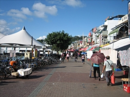 Pedestrians, bicycles, and stores on the waterfront at Hong Kong's Cheung Chau Harbor