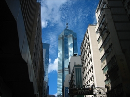 Skyscrapers (including the Center) rise into a blue sky over a street in downtown Hong Kong