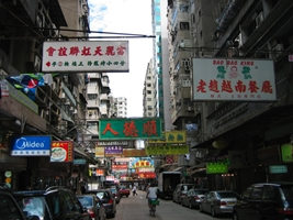 A narrow street walled in by buildings in the Kowloon area of Hong Kong
