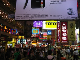 Large store billboards and crowds of shoppers near a night market in Hong Kong's Kowloon district