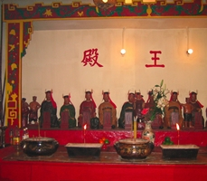 A row of Taoist idols with offerings of burning incense in Hong Kong's Man Mo Temple