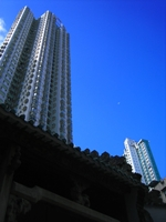 High-rise apartments looming over Man Mo Temple in downtown Hong Kong with a tiny moon visible in the sky