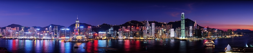 A panoramic view across Victoria Harbour from Kowloon of the brightly lit buildings of the downtown area of Hong Kong Island