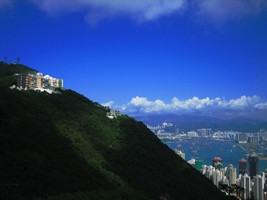 A closeup view of the side of Victoria Peak with Victoria Harbour and Kowloon in the background