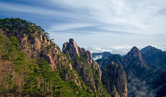 Peaks, trees, blue sky, and a distant sea of clouds in Huangshan (黄山, Yellow Mountain), China