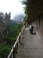 Tourists climb up a long, steep stairway ascending a mountain in Huangshan (黄山, Yellow Mountain), China