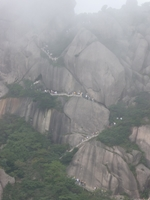 Tourists climb a long, steep, winding stairway through the fog in Huangshan (黄山, Yellow Mountain), China