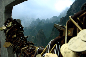 Locks symbolizing a romantic attachment between two people are tightly packed along a chain, with the mists and peaks of Yellow Mountain in the background, in Huangshan (黄山), China